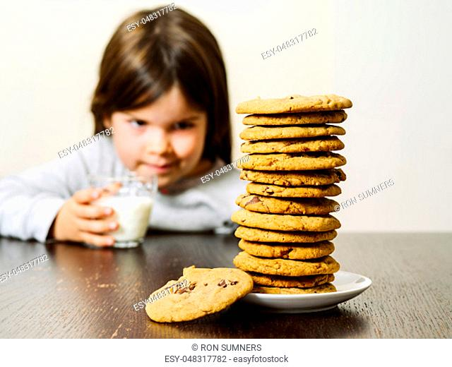 Photo of a young girl staring at a tall pile of chocolate chip cookies while holding a glass of milk. Focus on the cookies