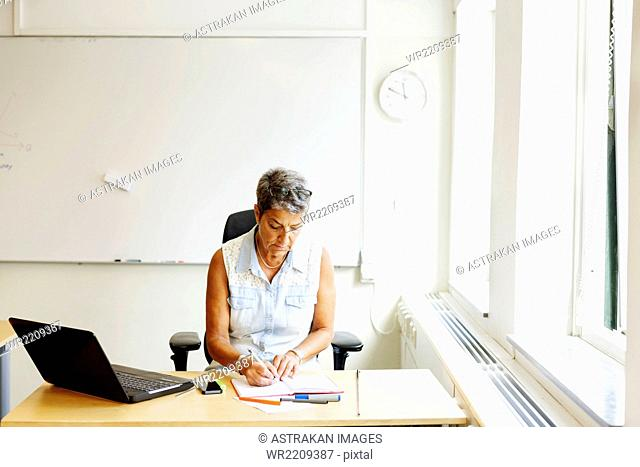 Mature female professor writing on book at desk in classroom