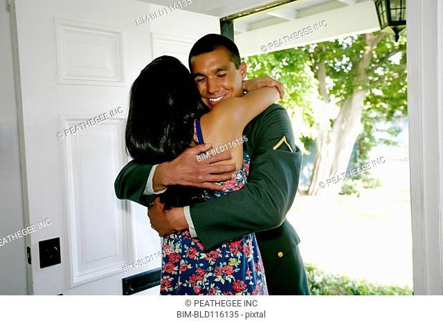 Woman hugging soldier boyfriend at door