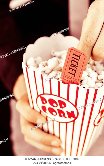 Still life photo on the hand of a person eating popcorn during vintage show. Popcorn box office