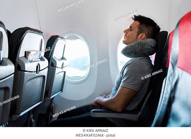 Man sleeping with neck pillow in airplane
