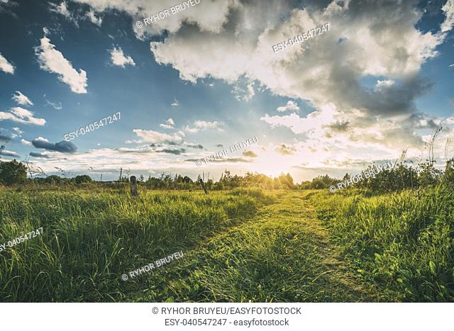 Beautiful Sunset, Sunrise Over Rural Meadow. Dramatic Sky And Country Road Path Way Lane. Countryside Landscape At Sunset Dawn Sunrise. Skyline