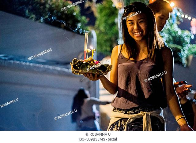 Young woman by Ping River in Chiang Mai during Loy Krathong Lantern Festival, releasing floating lantern down the Ping River, Chiang Mai, Thailand