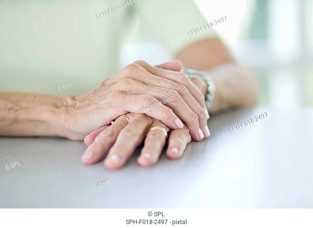 Senior woman with one hand on the other, close up