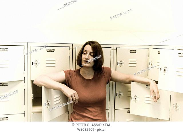 Young woman standing among a group of lockers