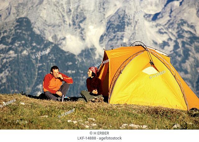 A couple breakfasting in front of a tent, Hutterer Hoess, Kalkalpen, Muehlviertel, Upper Austria