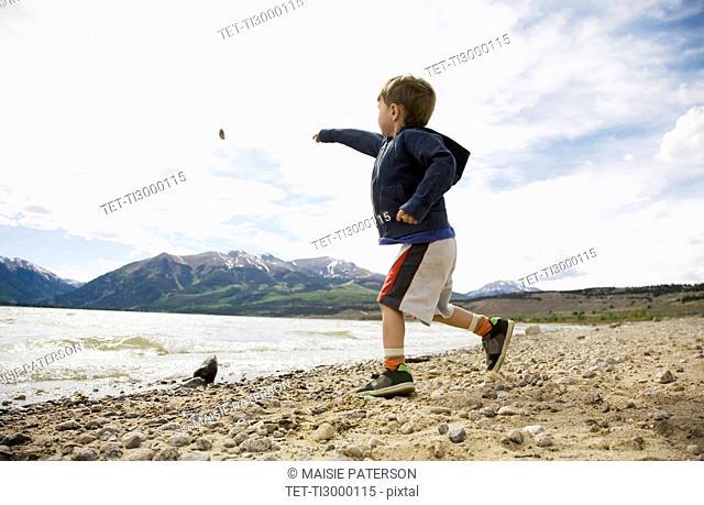 Boy 2-3 throwing rock in lake