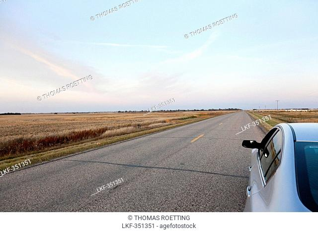 Parking car on a deserted road, fields, endless road, highway in the mid-west, Maxbass, Minot, North Dakota, United States of America, USA