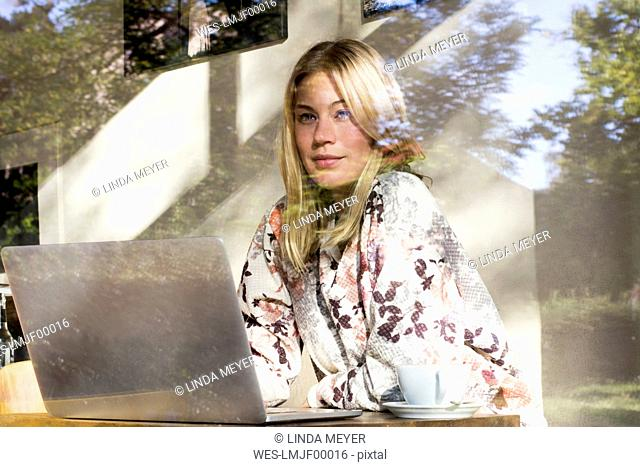 Portrait of blond woman with laptop sitting in a cafe looking out of window