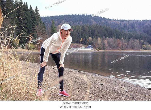 Female jogger having a rest at lakeshore