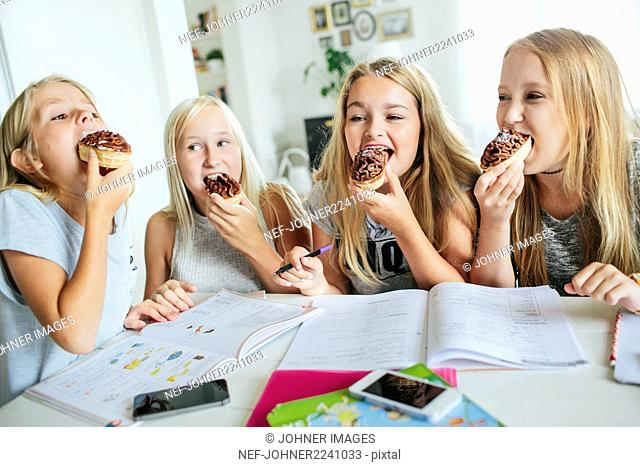 Girls having snack while they learning together