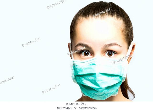 Cute young girl in doctors mask looking surprised, shocked and frightened