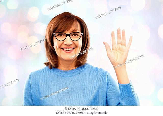 portrait of senior woman in glasses waving hand