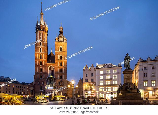 Night falls at St Mary's Basilica church on the Main Market Square in Kraków Old Town, Poland
