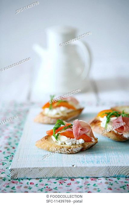 Crostini topped with cream cheese, apricots and ham