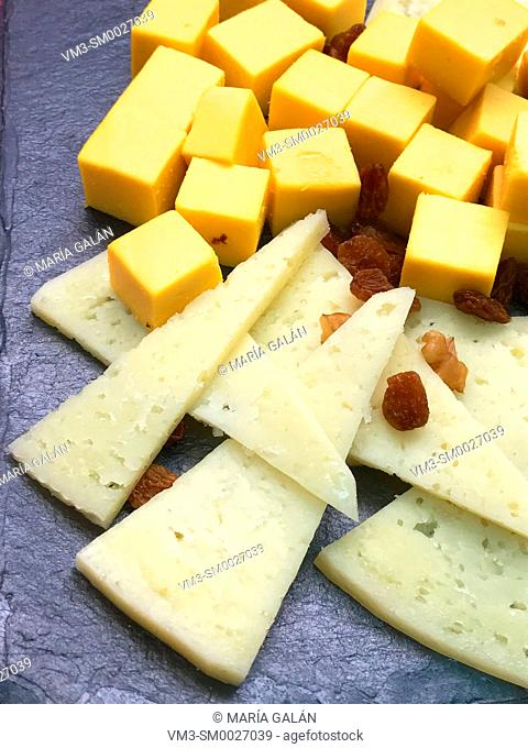 Assorted cheeses with raisng on slate dish