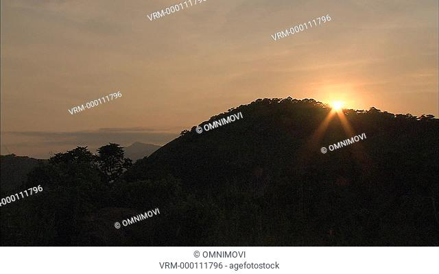 Sun setting behind tree covered hills with sun rays