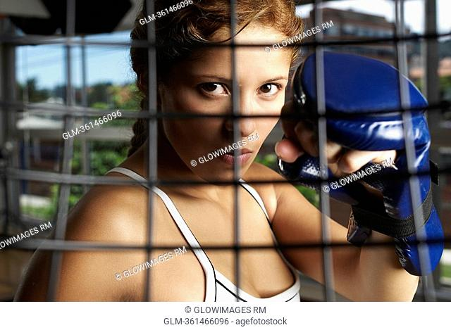 Portrait of a young woman wearing a boxing glove