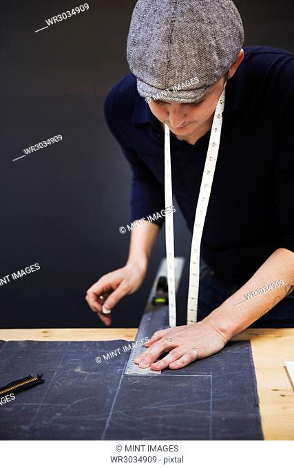 A man measuring up and marking with tailor's chalk, a piece of grey fabric using a metal ruler