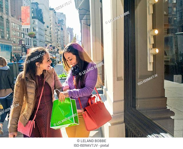 Young female adult twins looking into shopping bags on city sidewalk