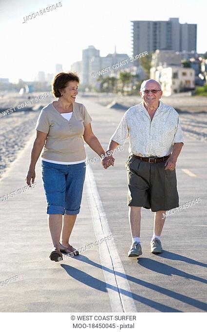 Senior couple on footpath along beach