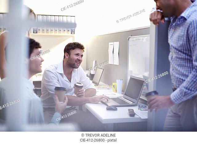 Architects talking and drinking coffee at laptop in office