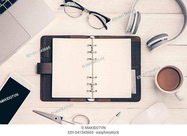 Top view on opened notebook, smartphone, laptop, eyeglasses, cup of coffee and other equipment on wooden office desk