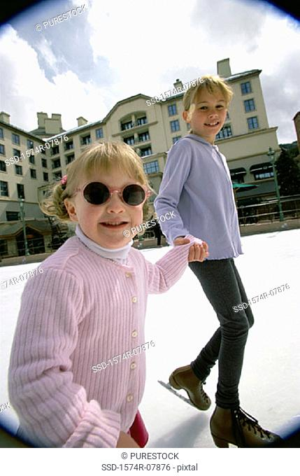 Portrait of two girls ice skating together