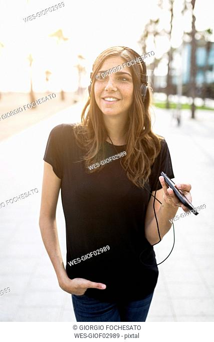 Smiling young woman on boardwalk listening to music