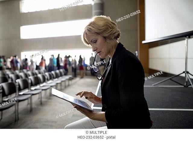 Focused professor with digital tablet preparing auditorium stage