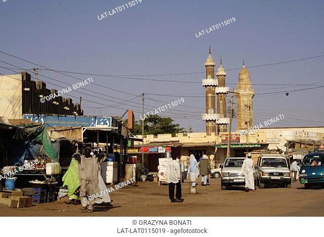 Small town. Market stalls. Road. Street. Traffic. Cars and vans. People. Walls and minaret of mosque. Muslim place of worship