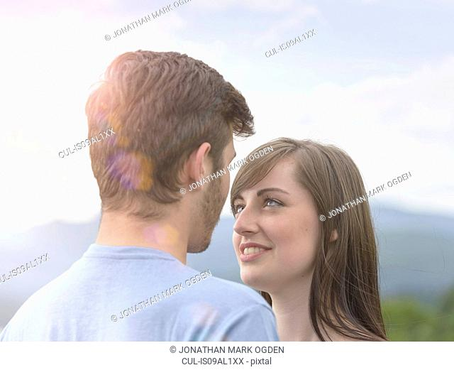 Young couple face to face under bright sunny sky