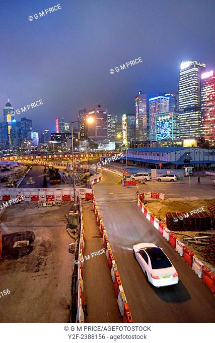 a white car drives along temporary construction site road with Hong Kong skyline in the background