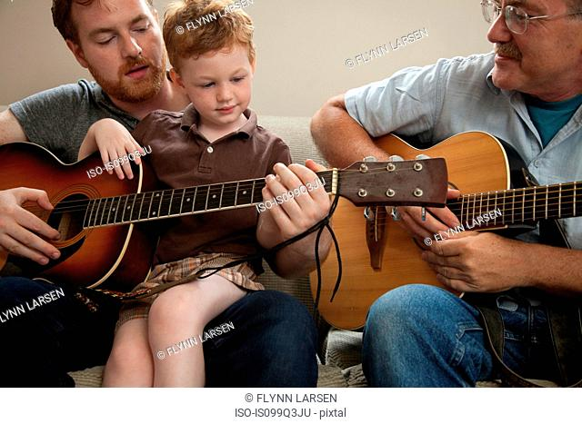 Father teaching son to play guitar, with grandfather