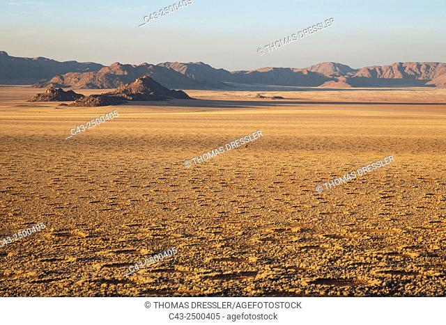 Grass-grown desert plain and isolated mountain ridges at the edge of the Namib Desert. The so-called Fairy Circles are circular patches without any vegetation...