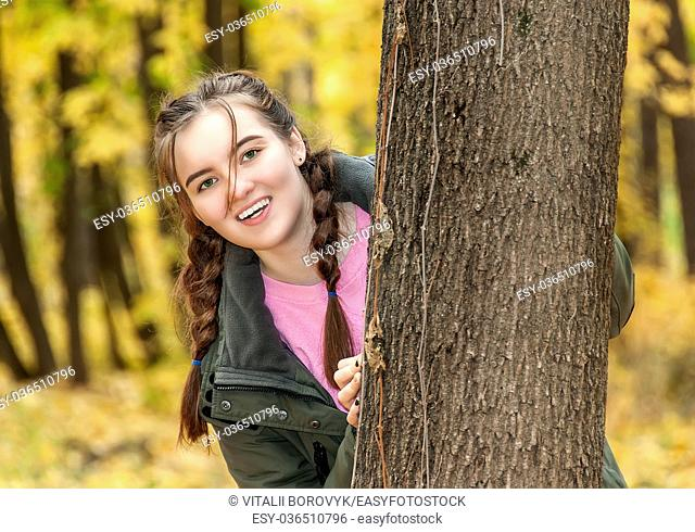 Laughing teen girl. A girl looks out from behind a tree in the park. Smiling happy face