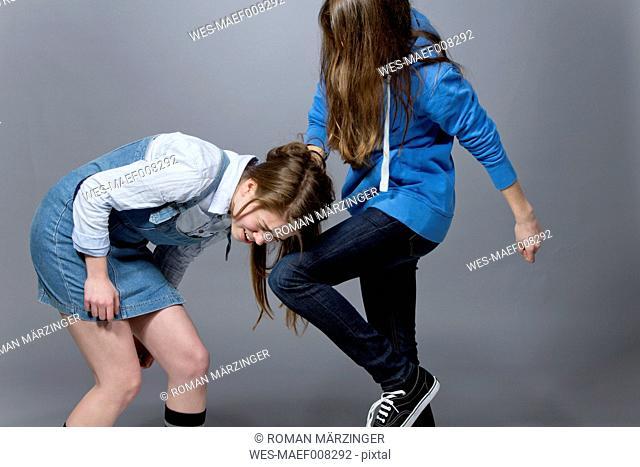 Teenage girl kicking her sister