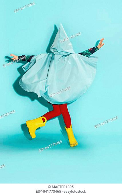 Little girl posing in fashion style wearing autumn clothing on blue background. Rubber yellow boots. Back view
