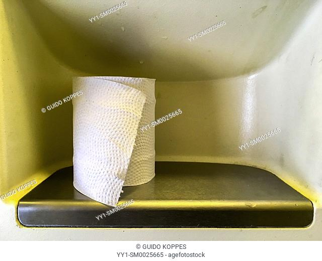 Intercity Train, Netherlands. Rol of toilet paper waiting te be deployed inside a intercity train toilet and restroom