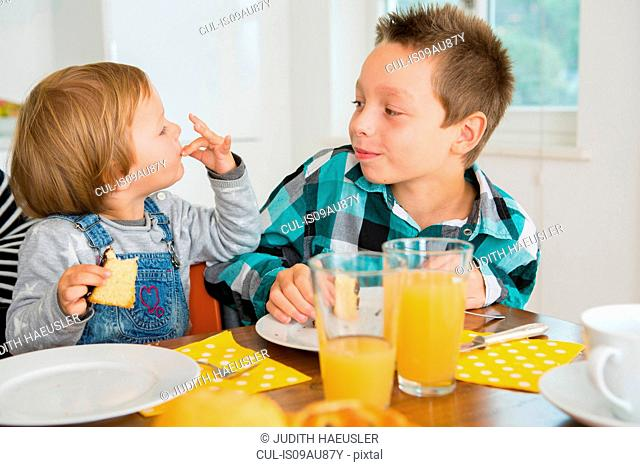 Cute female toddler licking fingers at kitchen table