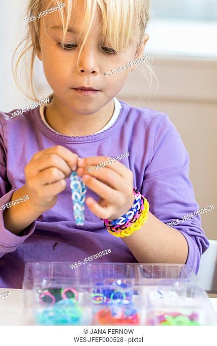 Portrait of little girl making loom bracelets