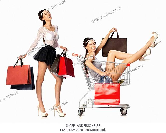 Collage, Smiling women posing next to an empty shopping cart isolated on white background