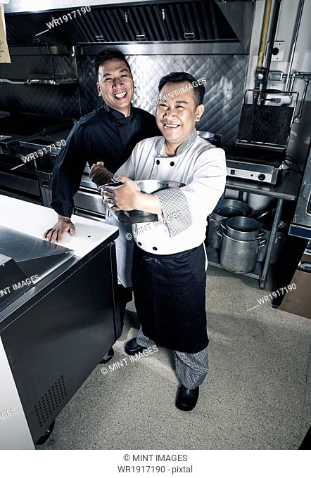 Two cooks in a commercial restaurant kitchen