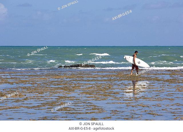 Man carrying surfboard at Praia do Forte, Bahia,Brazil
