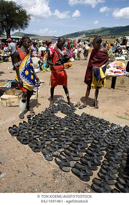 Weekly open air market in South kenya, bordering game park Â'Maasai MaraÂ', inhabited by the massai ethnic tribe Shoes are made from old tyres ands for sale on...