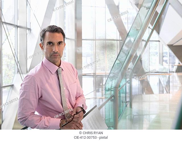 Portrait serious corporate businessman in modern office lobby