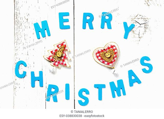 merry christmas words, christmas tree and decoration on wooden background