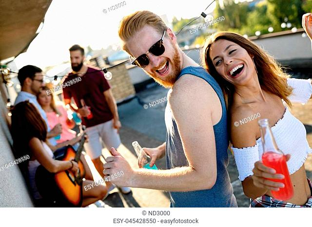 Group of friends having fun at rooftop party