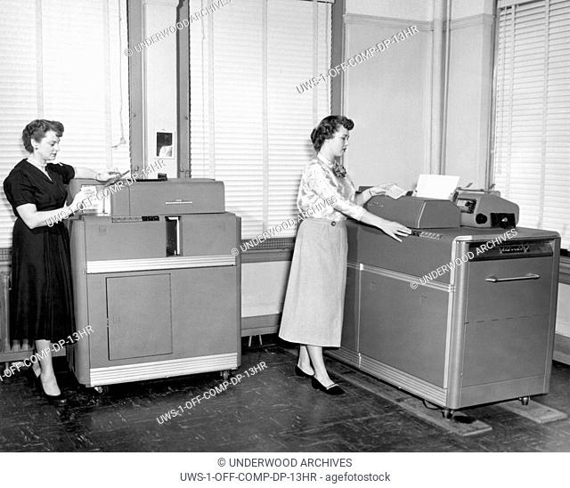 Cleveland, Ohio: c. 1954 .Women using two different IBM punch card machines. On the left is a Summary Punch Machine, and on the right is the type 407 Alphabetic...