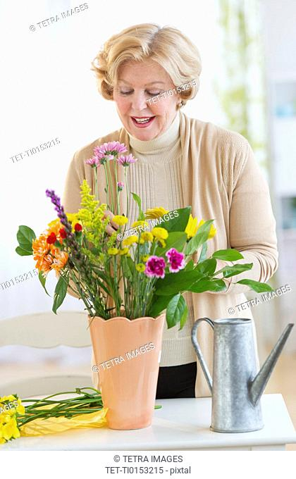Smiling senior woman arranging flowers